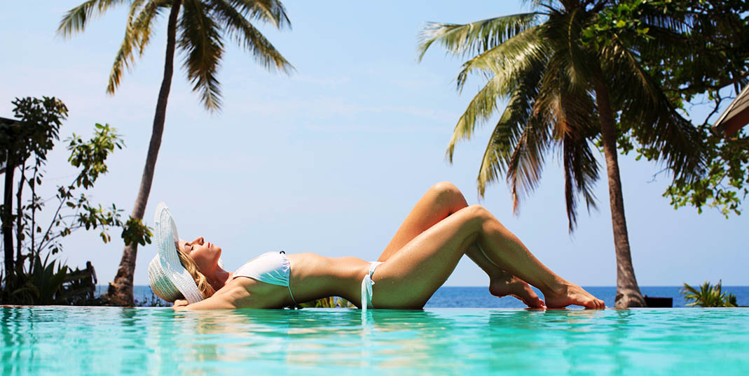 Beautiful woman lying on the edge of the swimming pool on the beach.